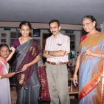 Presenting a certificate to a child: Asha, Bhasker and Nirmala